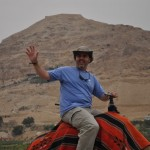 Friend riding a camel with the Mount of Temptations behind him.